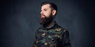 Πορτρέτο του γενειοφόρου διαστισμένου hipster αρσενικού που ντύνεται σε ένα στρατιωτικό σακάκι Στοκ φωτογραφία με δικαίωμα ελεύθερης χρήσης