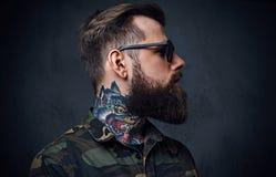 Πορτρέτο του γενειοφόρου διαστισμένου hipster αρσενικού που ντύνεται σε ένα στρατιωτικό σακάκι Στοκ Εικόνες