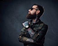 Πορτρέτο του γενειοφόρου διαστισμένου hipster αρσενικού που ντύνεται σε ένα στρατιωτικό σακάκι Στοκ Εικόνα