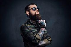 Πορτρέτο του γενειοφόρου διαστισμένου hipster αρσενικού που ντύνεται σε ένα στρατιωτικό σακάκι Στοκ Φωτογραφίες