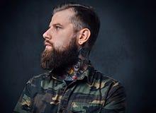 Πορτρέτο του γενειοφόρου διαστισμένου hipster αρσενικού που ντύνεται σε ένα στρατιωτικό σακάκι Στοκ εικόνες με δικαίωμα ελεύθερης χρήσης