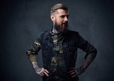 Πορτρέτο του γενειοφόρου διαστισμένου hipster αρσενικού που ντύνεται σε ένα στρατιωτικό σακάκι Στοκ Φωτογραφία