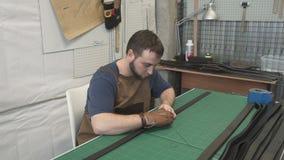 Πορτρέτο του γενειοφόρου εργαζομένου δέρματος που κάνει τις ζώνες στο στούντιο φιλμ μικρού μήκους