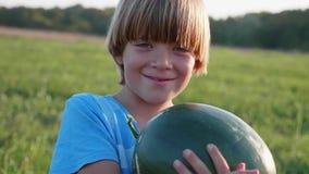 Πορτρέτο του γιου αγροτών ` s με ολόκληρο το καρπούζι στον τομέα του αγροκτήματος φιλμ μικρού μήκους