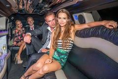 Πορτρέτο του γοητευτικού νέου ζεύγους με τους φίλους που κάθονται στο limou Στοκ Εικόνες
