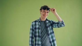 Πορτρέτο του δροσερού νεαρού άνδρα που βγάζει τα γυαλιά ηλίου και που χαμογελά την εξέταση τη κάμερα απόθεμα βίντεο