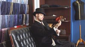 Πορτρέτο του ελκυστικού ατόμου στο σκοτεινό παλτό και των καθιερωνόντων τη μόδα ραφτών κοστουμιών στο εσωτερικό φιλμ μικρού μήκους