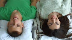 Πορτρέτο του ελκυστικού ζεύγους που χαμογελά στην κρεβατοκάμαρα φιλμ μικρού μήκους