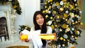 Πορτρέτο του ελκυστικού κοριτσιού στην καλή διάθεση με το δώρο στα χέρια, που χαμογελά στη κάμερα και που κάθεται στο υπόβαθρο τω απόθεμα βίντεο