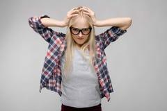 Πορτρέτο του ελκυστικού κουρασμένου γλυκού λατρευτού ξανθού κοριτσιού εφήβων στα ελεγμένα ενδύματα στα γυαλιά με τα χέρια στο κεφ στοκ φωτογραφία με δικαίωμα ελεύθερης χρήσης