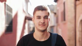 Πορτρέτο του ελκυστικού μοντέρνου νεαρού άνδρα που εξετάζει τη κάμερα και το χαμόγελο απόθεμα βίντεο