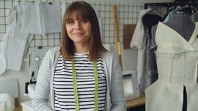Πορτρέτο του ελκυστικού νέου σχεδιαστή ιματισμού γυναικών με την καφετιά τρίχα που εξετάζει τη κάμερα Η χαμογελώντας γυναίκα στέκ απόθεμα βίντεο