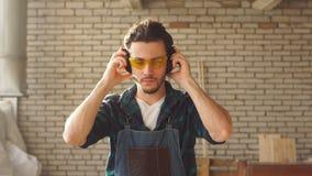 Πορτρέτο του ελκυστικού νέου όμορφου ξυλουργού που κλίνεται στον πίνακα στο εργαστήριο φιλμ μικρού μήκους