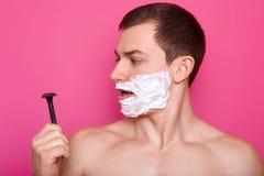 Πορτρέτο του ελκυστικού νεαρού άνδρα με τον αφρό παντού το πρόσωπό του που εξετάζει το ξυράφι στεμένος με τη σοβαρή έκφραση του π στοκ εικόνες