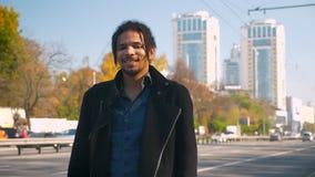 Πορτρέτο του ελκυστικού τύπου αφροαμερικάνων με τα dreadlocks που χαμογελούν ήρεμα στη κάμερα στο οδικό υπόβαθρο απόθεμα βίντεο