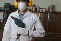 Πορτρέτο του επαγγελματικού νέου ασιατικού ξυλουργού με ηλεκτρικό τρυπάνι εκμετάλλευσης ασφάλειας το ομοιόμορφο στο υπόβαθρο εργα στοκ φωτογραφία
