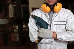 Πορτρέτο του επαγγελματικού νέου εργαζομένου με ηλεκτρικό τρυπάνι εκμετάλλευσης ασφάλειας το ομοιόμορφο στο εργαστήριο ξυλουργική στοκ φωτογραφία