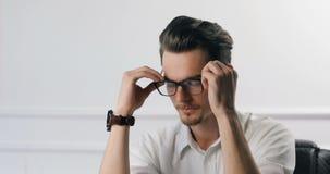 Πορτρέτο του επιτυχούς νέου ευτυχούς έξυπνου επιχειρηματία στην αρχή Καθορίστε τα γυαλιά και το χαμόγελό του 4k απόθεμα βίντεο