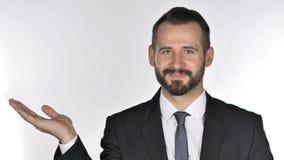Πορτρέτο του επιχειρηματία γενειάδων που παρουσιάζει προϊόν στο δευτερεύον, άσπρο υπόβαθρο απόθεμα βίντεο