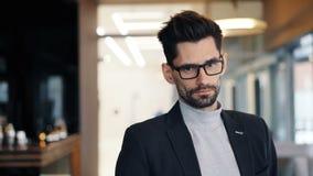 Πορτρέτο του επιχειρηματία που εξετάζει τη κάμερα με το σοβαρό πρόσωπο που στέκεται στον καφέ απόθεμα βίντεο