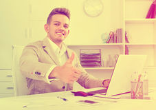 Πορτρέτο του επιχειρηματία που παρουσιάζει αντίχειρες στο σύγχρονο γραφείο Στοκ Φωτογραφίες
