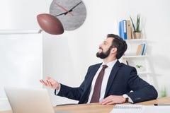 πορτρέτο του επιχειρηματία που ρίχνει τη σφαίρα ράγκμπι στον εργασιακό χώρο με το lap-top Στοκ Φωτογραφίες