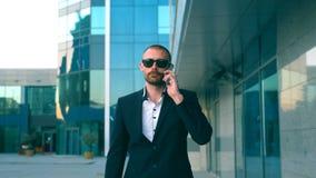 Πορτρέτο του επιχειρηματία στα γυαλιά ηλίου που μιλούν στο τηλέφωνο και που περπατούν στην οδό Νεαρός άνδρας που έχει την επιχειρ απόθεμα βίντεο