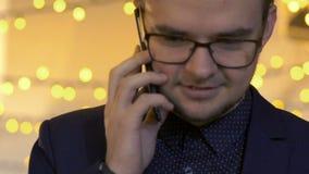 Πορτρέτο του επιχειρηματία στα γυαλιά, που μιλά στο τηλέφωνο και που χαμογελά αργά απόθεμα βίντεο