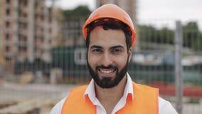 Πορτρέτο του εργάτη οικοδομών στο πορτοκαλί κράνος που χαμογελά στη κάμερα Ο οικοδόμος στέκεται ενάντια στο σκηνικό του α απόθεμα βίντεο
