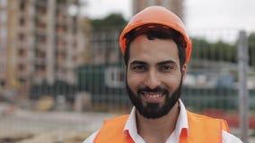 Πορτρέτο του εργάτη οικοδομών στο πορτοκαλί κράνος που χαμογελά στη κάμερα Ο οικοδόμος στέκεται ενάντια στο σκηνικό του α φιλμ μικρού μήκους