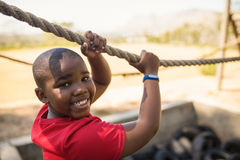 Πορτρέτο του ευτυχούς αγοριού που διασχίζει το σχοινί κατά τη διάρκεια της σειράς μαθημάτων εμποδίων Στοκ Εικόνα