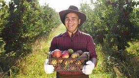 Πορτρέτο του ευτυχούς αγρότη στο καπέλο που στέκεται στον κήπο μήλων απόθεμα βίντεο
