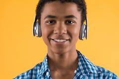 Πορτρέτο του ευτυχούς αμερικανικού εφήβου afro στα ακουστικά στοκ εικόνα με δικαίωμα ελεύθερης χρήσης