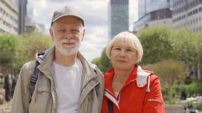 Πορτρέτο του ευτυχούς ανώτερου ζεύγους που στέκεται στην οδό εξέταση τη κάμερα Τοπίο πόλεων στο υπόβαθρο απόθεμα βίντεο