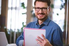 Πορτρέτο του ευτυχούς ανώτερου υπαλλήλου με τα έγγραφα στο γραφείο Στοκ εικόνες με δικαίωμα ελεύθερης χρήσης