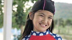 Πορτρέτο του ευτυχούς ασιατικού κοριτσιού που φορά το κολυμπώντας κοστούμι που εξετάζει τη κάμερα φιλμ μικρού μήκους