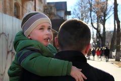 Πορτρέτο του ευτυχούς ατόμου που κρατά το γιο του στο λαιμό στο υπόβαθρο του ουρανού στοκ φωτογραφία με δικαίωμα ελεύθερης χρήσης