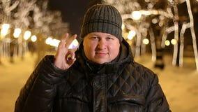Πορτρέτο του ευτυχούς ατόμου που παρουσιάζει εντάξει σημάδι υπαίθρια κατά τη διάρκεια του κρύου χειμερινού βραδιού απόθεμα βίντεο