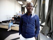 Πορτρέτο του ευτυχούς αφρικανικού τύπου που εξετάζει τη κάμερα στο εργασιακό περιβάλλον Στοκ Φωτογραφία
