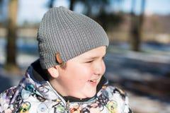 Πορτρέτο του ευτυχούς γελώντας παχιού παιδιού στην ΚΑΠ και του χειμερινού σακακιού στο πάρκο το χειμώνα Στοκ φωτογραφία με δικαίωμα ελεύθερης χρήσης