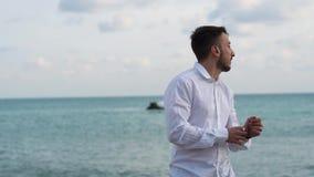 Πορτρέτο του ευτυχούς γενειοφόρου ατόμου που στέκεται κοντά στη θάλασσα Νέες στάσεις τύπων ήρεμα στην ακτή φιλμ μικρού μήκους