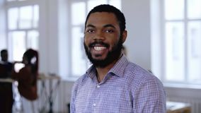 Πορτρέτο του ευτυχούς επαγγελματικού μαύρου επιχειρηματία επιχειρηματιών με τη γενειάδα και της όμορφης τοποθέτησης χαμόγελου στο φιλμ μικρού μήκους