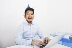 Πορτρέτο του ευτυχούς επιχειρηματία που φορά το καπέλο κομμάτων εργαζόμενος στην αρχή Στοκ φωτογραφίες με δικαίωμα ελεύθερης χρήσης