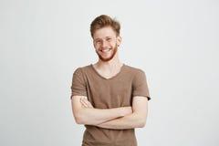 Πορτρέτο του ευτυχούς εύθυμου νεαρού άνδρα με το χαμόγελο γενειάδων που εξετάζει τη κάμερα με τα διασχισμένα όπλα πέρα από το άσπ Στοκ εικόνες με δικαίωμα ελεύθερης χρήσης