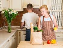 Πορτρέτο του ευτυχούς ζεύγους με την τσάντα εγγράφου παντοπωλείων με τα λαχανικά στοκ εικόνες