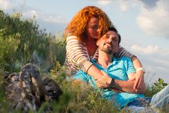 Πορτρέτο του ευτυχούς ζεύγους που βάζει στο κάλυμμα στη χλόη κοντά στην εστία στο υπόβαθρο σύννεφων στοκ φωτογραφίες με δικαίωμα ελεύθερης χρήσης