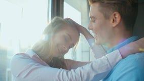 Πορτρέτο του ευτυχούς ζεύγους που στέκεται μαζί κοντά στο παράθυρο απόθεμα βίντεο