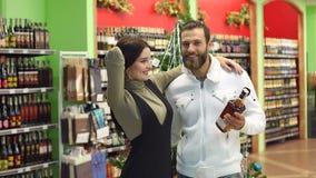 Πορτρέτο του ευτυχούς ζεύγους στο κατάστημα υπεραγορών ή κρασιού Αγορές για τα Χριστούγεννα φιλμ μικρού μήκους