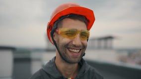 Πορτρέτο του ευτυχούς και βέβαιου οικοδόμου αρχιτεκτόνων με το κράνος ασφάλειας στο εργοτάξιο οικοδομής, που χαμογελά στη κάμερα φιλμ μικρού μήκους