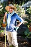 Πορτρέτο του ευτυχούς κηπουρού που στέκεται με το εργαλείο στον κήπο Στοκ εικόνες με δικαίωμα ελεύθερης χρήσης